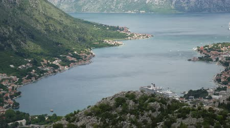 kotor : Bay of Kotor from the heights. View from Mount Lovcen to the bay. View down from the observation platform on the mountain Lovcen. Mountains and bay in Montenegro. The liner near the old town of Kotor.
