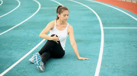 Runner stretching on the running track.