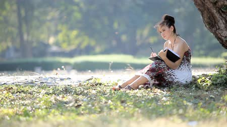 Woman writing in notepad by pen at sunny summer