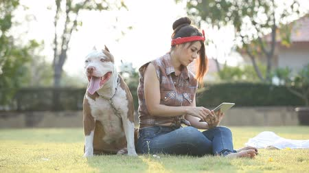 Woman with dog and holding a tablet.