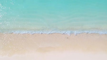 Shot from above of shallow water waves hitting the white sandy beach 影像素材