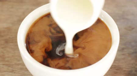 hot beverage : Adding milk to a cup of hot americano, Stock Video