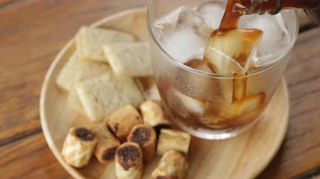 coffee brewing : Serving glass of black iced coffee with some snack, stock video Stock Footage