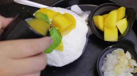 desszertek : Woman Topping Mango Sauce On Dessert, stock video
