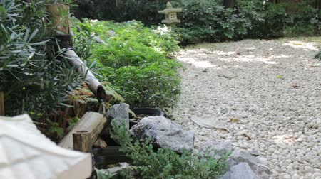 zen como : Water flowing out of a wooden spout into a japanese stone garden, stock footage