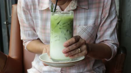 Woman enjoy drinking iced green tea latte, stock footage