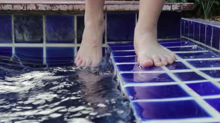 Dipping toe in swimming pool, stock footage