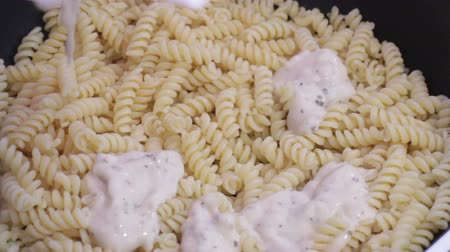 Pouring pasta and cooking in nonstick pan, stock footage