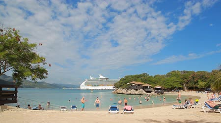 LABADEE, HAITI - APRIL 16, 2017: Tropical beach with Royal Caribbean cruise ship Navigator of the Seas docked at the private port of Labadee in the Caribbean Island of Haiti