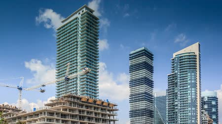 Timelapse of constraction site and residential high rise buildings with moving white clouds in blue sky, Toronto