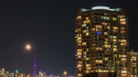 Timelapse of residential high rise buildings at night with moving moon in Toronto