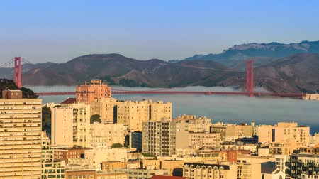 Sunny morning in San Francisco with fog flowing under the Golden Gate Bridge 影像素材