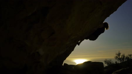 сумерки : Rock Climbing Silhouette - A rock climber at sunset. Стоковые видеозаписи