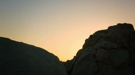low lighting : Desert Boulders At Sunset - Motion control slider reveal left and right of summer sunset behind Joshua Tree National Park boulders. Stock Footage