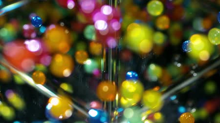 разброс : Bouncy Ball Rainbow - High speed macro shot of colorful bouncy balls falling against a reflective surface.