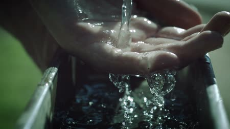 освещенный : Slow Motion Water Over Hand - Super slow motion profile shot of a stream of water falling into a hand and beading and splashing around in high speed.