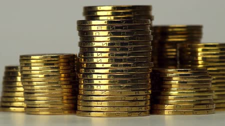 mince : Several Columns of Coins Spinning on a Light Background