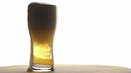 pint glass : Beer is Poured into a Tall Glass Standing on a Wooden Board on a Light Background