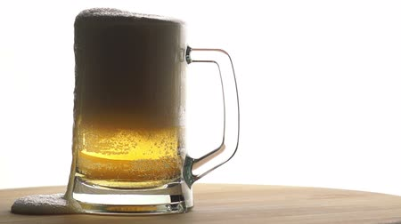 bögre : Beer is Poured into a Mug Standing on a Wooden Board on a Light Background Stock mozgókép