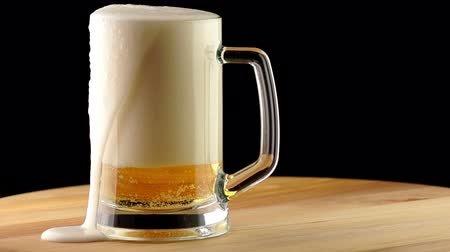 bögre : Light Beer is Poured into a Mug Standing on a Wooden Board on a Dark Background