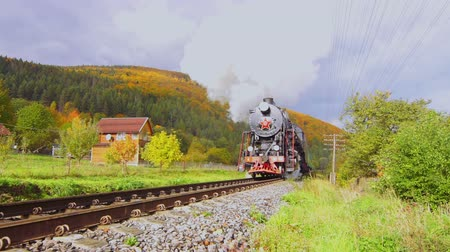 mozdony : Old Steam Locomotive Moves on Rails Between the Hills