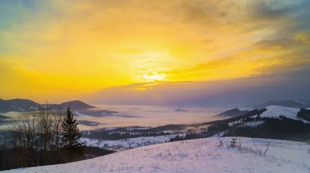 vadon terület : Foggy Morning in the Winter Mountains Forest on the Background of Dramatic Cloudy Sky. Timelapse. Stock mozgókép