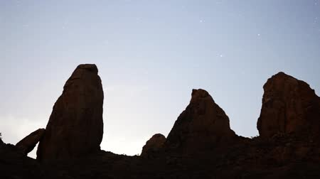 стрельба : Motion controlled dolly time lapse footage with zoom out motion of moon rising over monolithic formation in the desert of Trona