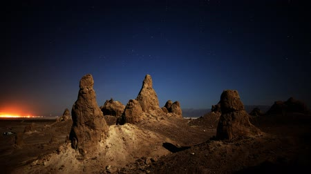 trona : Astrophotography time lapse with tilt down motion of night to day transition over eroded formation in Trona Pinnacles Stock Footage