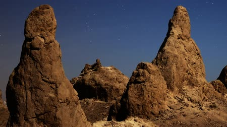 trona : Astrophotography time lapse with pan right motion of night to day transition over eroded formation in Trona Pinnacles Stock Footage