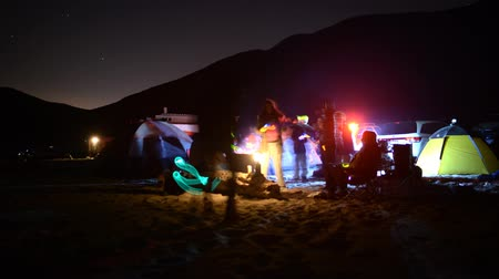 приморский : Time lapse footage with tilt up motion of campers enjoying company at night on the Beach in Malibu