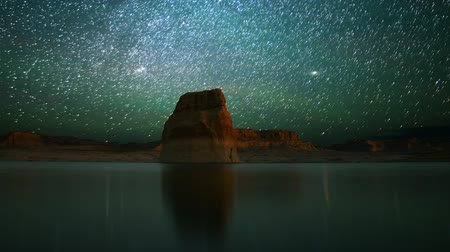 стрельба : Astrophotography time lapse footage with pan left motion of star trails over lone rock in Lake Powell Стоковые видеозаписи