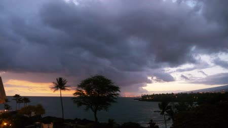 monszun : Time lapse footage with tilt down motion of cloudscape over beach resort during sunset afterglow at Kona Stock mozgókép