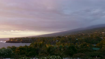 monszun : Time lapse footage with zoom in motion of cloudscape over beach resort during sunset afterglow at Kona Stock mozgókép