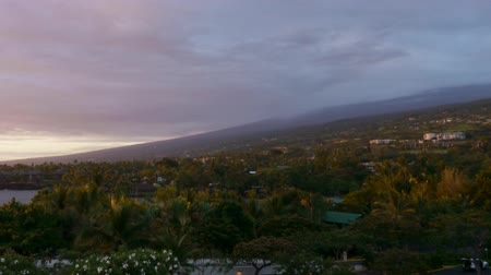 monszun : Time lapse footage with pan left motion of cloudscape over beach resort during sunset afterglow at Kona Stock mozgókép