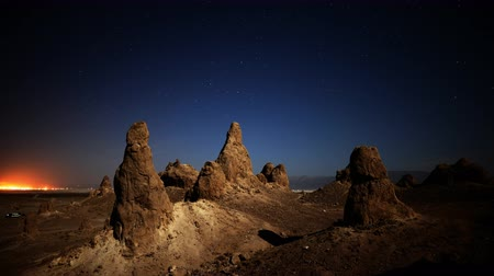 trona : 4K astrophotography time lapse with tilt down motion of night to day transition over eroded formation in Trona Pinnacles