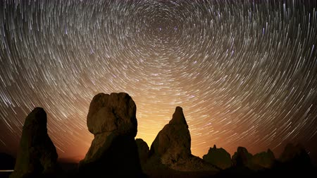 trona : 4K Astrophotography time lapse footage with tilt up motion of star trails over monolithic formations in Trona Pinnacles Stock Footage