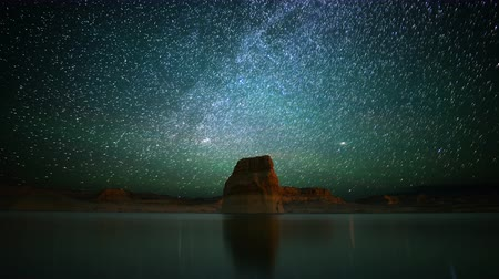 стрельба : 4K Astrophotography time lapse footage with tilt up motion of star trails over lone rock in Lake Powell