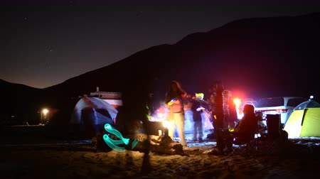 Калифорния : 4K time lapse footage with zoom in motion of campers enjoying company at night on the Beach in Malibu California Стоковые видеозаписи