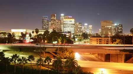 fari : 4K Time Lapse di Los Angeles Skyline sopra Freeway Bridge at Night Zoom In Filmati Stock