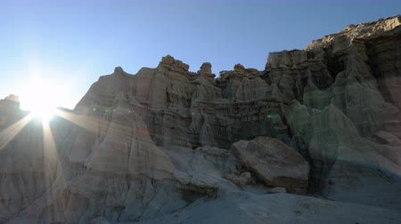 sinema : 4K Time Lapse of Sun Shining through Sandstone Formation Pan Left