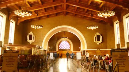 crowded : Time Lapse footage with zoom in motion of commuters in the historic hallway at Union Station in Los Angeles, California USA Stock Footage