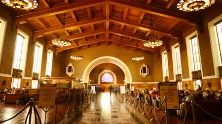 train workers : 4K time Lapse footage with pan left motion of commuters in the historic hallway at Union Station in Los Angeles, California USA