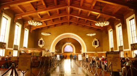Калифорния : 4K time Lapse footage with zoom out motion of commuters in the historic hallway at Union Station in Los Angeles, California USA