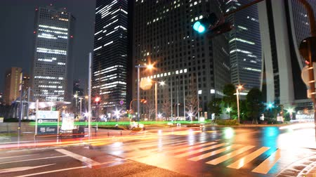 útkereszteződés : Motion controlled pan right  tilt up time lapse footage with zoom out motion of skyscrapers over an intersection in the rain at night in Shinjuku, Tokyo, Japan Stock mozgókép
