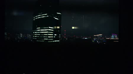 winda : Footage of urban cityscape of Tokyo at night shot from descending elevator in office building in Japan
