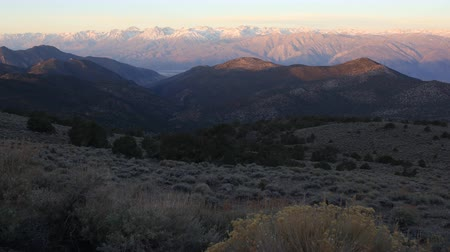 проливая : Time lapse footage of sunlight shining over snowcapped Sierra Nevada mountain range at Sunrise in White Mountains, California -Long Shot- Стоковые видеозаписи