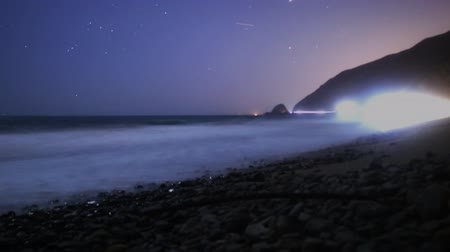 árapály : Time lapse footage with tilt up motion of coastal seascape from sunset into starry night in Malibu Beach, California