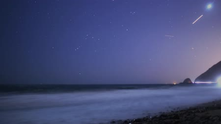 árapály : Time lapse footage with pan right motion of coastal seascape from sunset into starry night in Malibu Beach, California