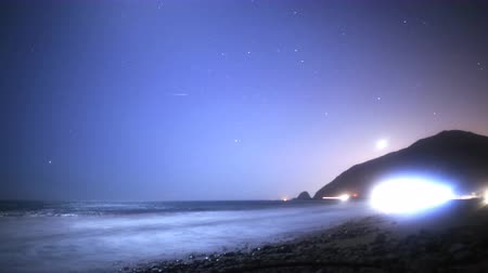árapály : Astrophotography time lapse footage with zoom in motion of moonlit coastline in Malibu Beach, California