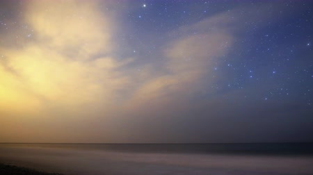 стрельба : Astrophotography Time Lapse footage with pan right motion of Milky Way galaxy rising over Night Seascape with scattered clouds in Malibu Beach, California